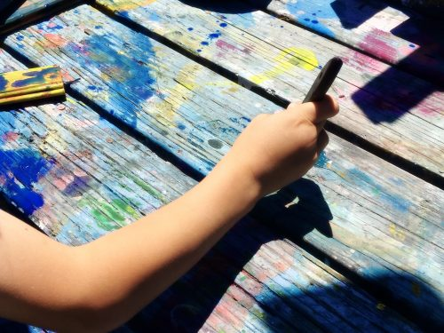 Image of Ross Valley Charter progressive education student painting a picnic table