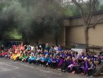 Ross Valley Charter students celebrate diversity by each class wearing a different color of the rainbow. Image shows classes in a row to make the rainbow