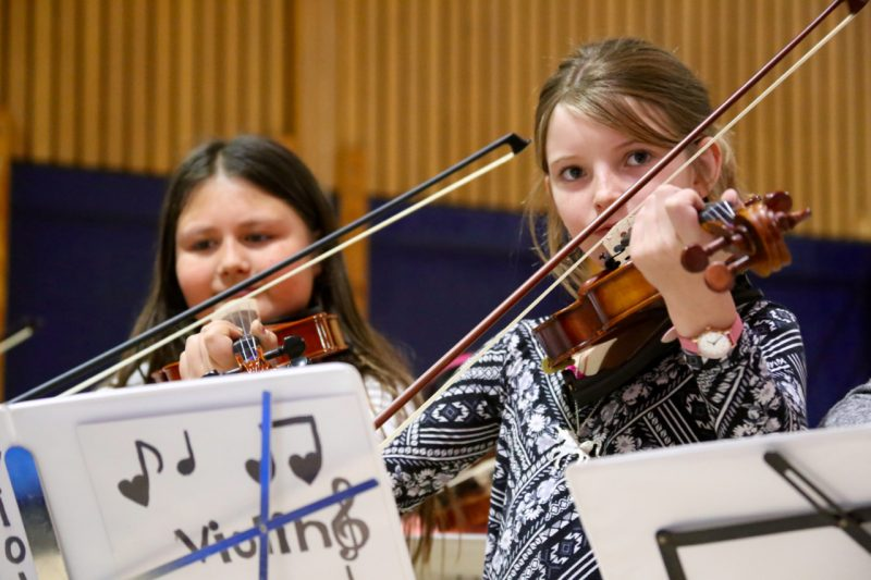 Fourth Grade elementary school students play violin at the music recital