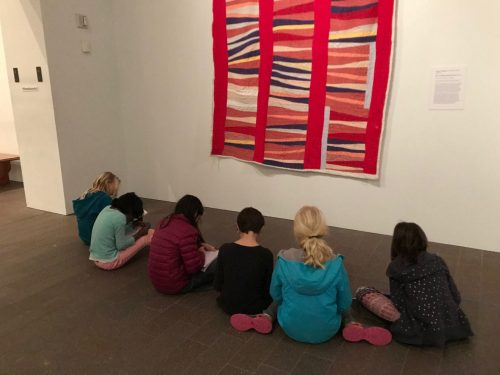 Ross Valley Charter Students write poetry while sitting on the floor of the de Young Museum