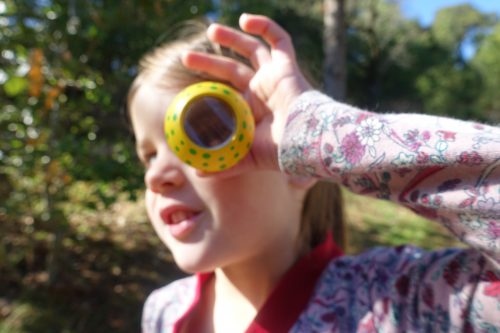 Transitional Kindergarteners enjoy imagination play and outdoor exploration. In this image, a young girl stands with Ross Valley Charter students holding a kaleidoscope