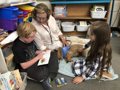 Ross Valley Reading Dog Program Volunteer with students and small dog.