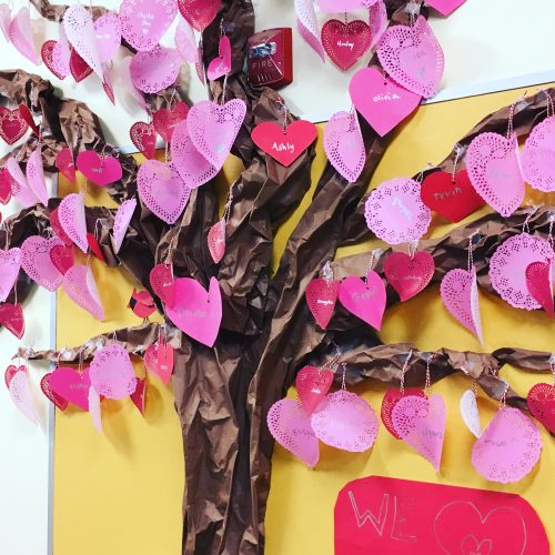 Multi-age elementary school students created a tree with hearts for leaves to celebrate spring.