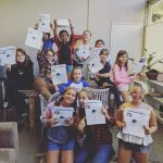Elementary school newspaper staff holding the first edition of their newspaper.