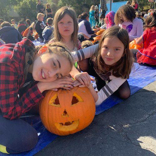 Progressive elementary school students work together to carve jack o'lanterns