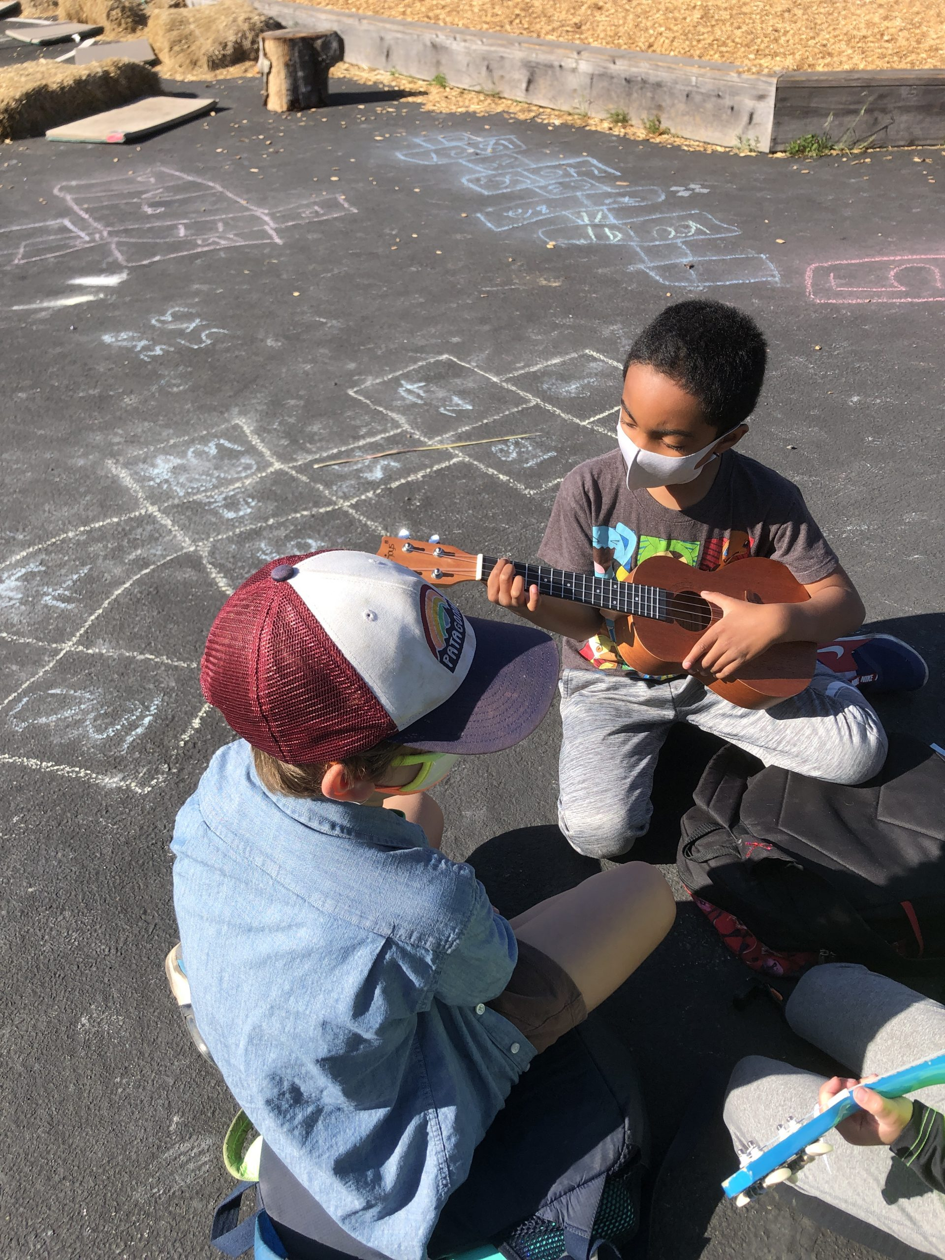 Charter students play music, two boys playing music on ukeleles